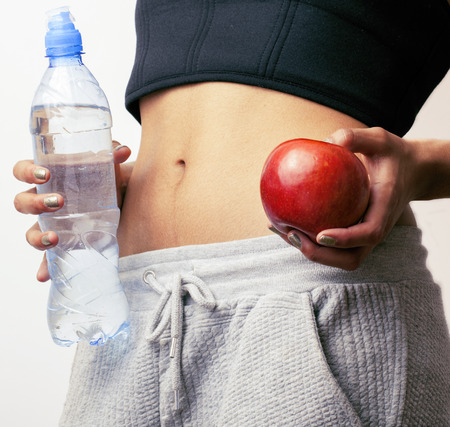woman measuring waist with red apple and water, african tann isolated close up Banco de Imagens