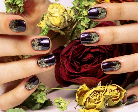 close up picture of manicure nails with dry flower red rose, dehydrated by winter cold photo