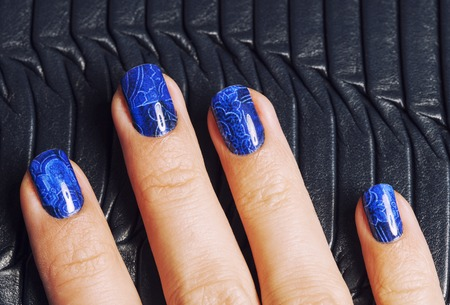 and of blue: pretty fingers, deep blue manicure close up with purse, luxury design indigo Stock Photo