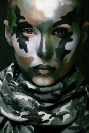 army face: Beautiful young fashion woman with military style clothing and face paint make-up, khaki colors green