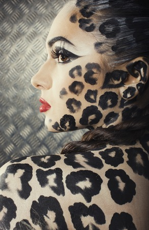animal eye: young sexy woman with leopard make up all over body, cat bodyart closeup creative