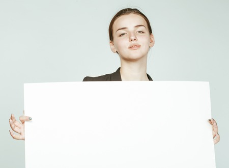 business costume: young pretty brunette girl with placard on white background wearing business costume