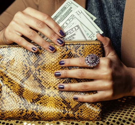 pretty fingers of african american woman holding money close up with purse, luxury jewellery on python clutch, cash for gifts manicure Stockfoto