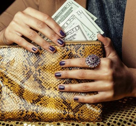 mooie vingers van de Afro-Amerikaanse vrouw aanhouden van geld close up met beurs, luxe juwelen op python clutch, contant geld voor cadeaus manicure