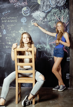 normal school: back to school after summer vacations, two teen real girls in classroom with blackboard painted together Stock Photo