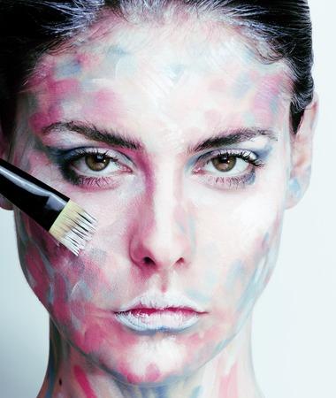 mujer joven con creativo componen como imagen al óleo pintada en la cara de cerca