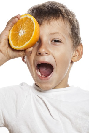 front teeth: little cute boy with orange fruit isolated on white smiling without front teeth Stock Photo