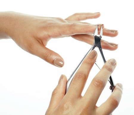 depraved: woman hands making no qualified manicure to herself isolated with tools Stock Photo