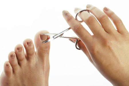 depraved: woman hands making no qualified pedicure to herself isolated with tools Stock Photo