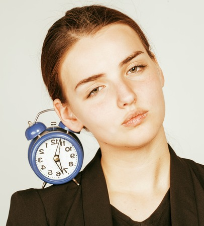 business costume: young beauty woman in business style costume waking up for work early morning on white background with clock Stock Photo