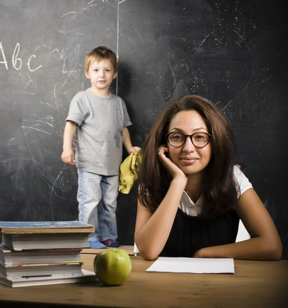 school desk: little cute boy in glasses with young real teacher, classroom studying at blackboard