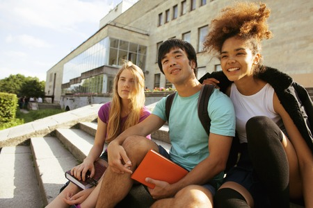 happy teenagers: cute group of teenages at the building of university with books huggings, smiling, back to school