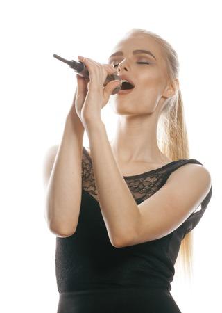 젊은 꽤 금발 여자가 격리 된 마이크에서 노래를 닫습니다. 스톡 콘텐츠
