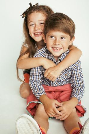 gemelos ni�o y ni�a: peque�o muchacho lindo y ni�a abrazando juega en el fondo blanco, familia feliz
