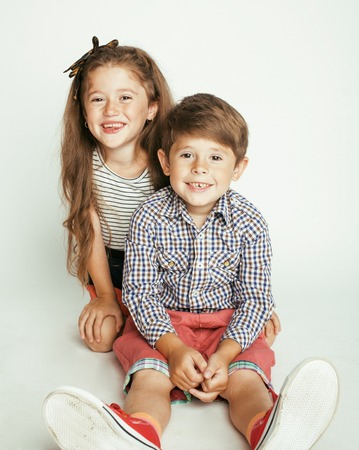 babies playing: little cute boy and girl hugging  playing on white background, happy family
