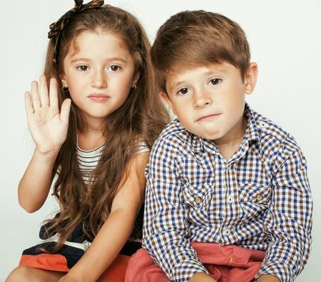 gemelas: pequeño muchacho lindo y niña abrazando juega en el fondo blanco, familia feliz