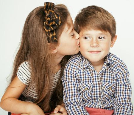 gemelos niÑo y niÑa: pequeño muchacho lindo y niña abrazando juega en el fondo blanco, familia feliz