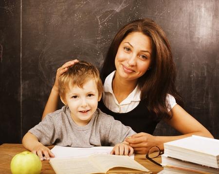 maestro: pequeño muchacho lindo en vidrios con el verdadero maestro joven, aula de estudio en la escuela pizarra Foto de archivo