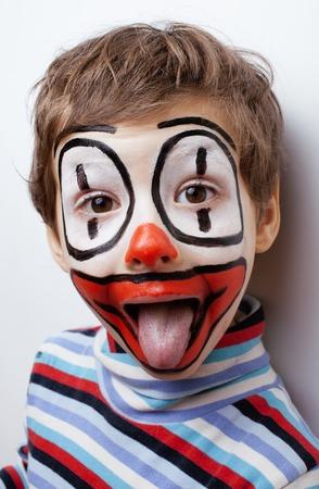 circo: poco niño de verdad lindo con facepaint como payaso, expresiones pantomímicas de cerca