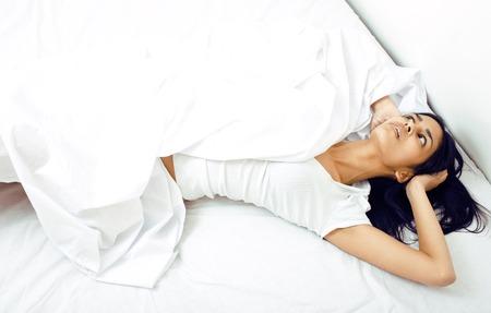 かなり本当のムラートのベッドでブルネットの女性、できない睡眠怒って見ることクローズ アップ白