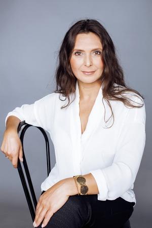 pretty brunette confident mature woman sitting on chair in studio Standard-Bild