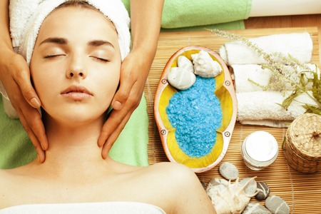 stock photo aantrekkelijke dame krijgt spa-behandeling in de salon, close-up Aziatische tan handen op gezicht Stockfoto