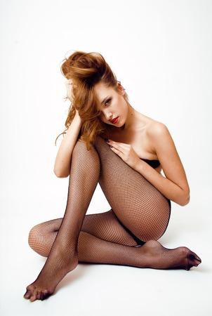 mujer desnuda: Verdadera mujer joven atractiva en pantimedias negro y lencería, labios rojos, mirada sexy aislados en fondo blanco Foto de archivo