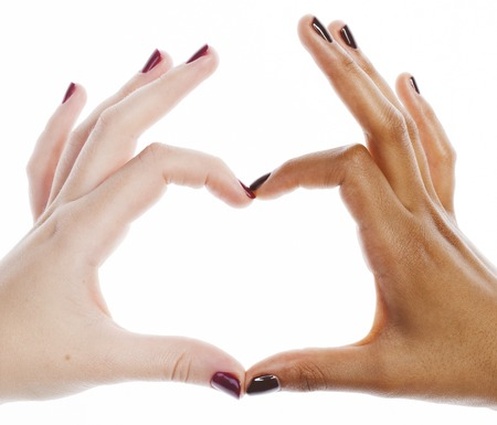 manicured hands: two different nathion manicured hands on white isolated, african with caucasian, shape of heart
