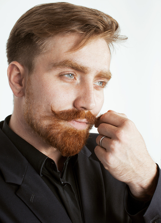 contemporary style: young red hair man with beard and mustache in black suit on white background close up