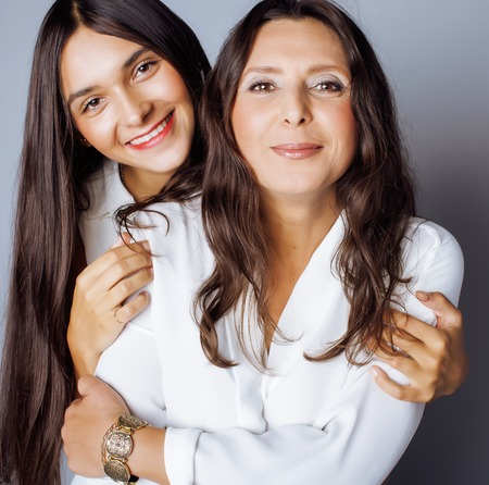 teens: cute pretty teen daughter with mature mother hugging, fashion style brunette makeup Stock Photo