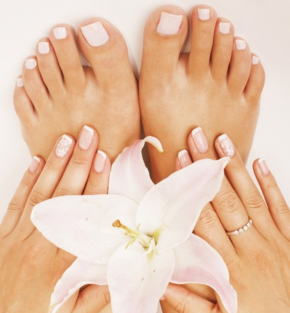 french pedicure: manicure pedicure with flower lily close up isolated on white perfect shape hands Stock Photo