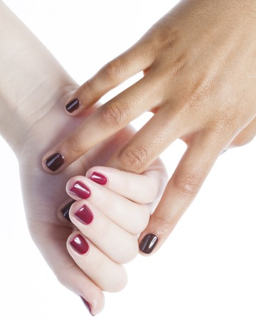 manicured hands: two different nathion manicured hands on white isolated, african with caucasian close up