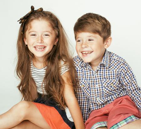 gemelos ni�o y ni�a: peque�o muchacho lindo y ni�a abrazando juega en el fondo blanco, verdadera familia feliz