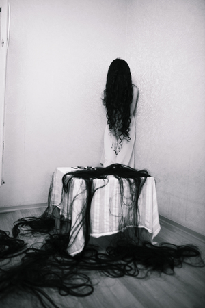 fearing: beauty girl cuting her hair in empty fearing room halloween ghost black and white