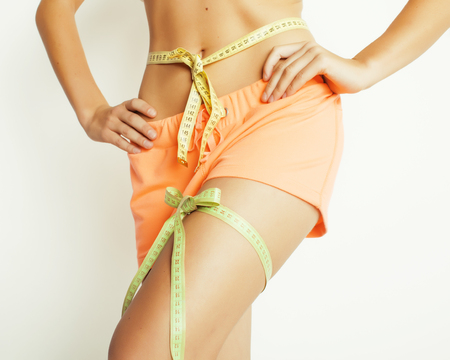 bow belly: woman measuring waist with tape on knot like a gift, tann isolated close up white background