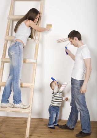 competent: portrait of happy family doing repair, new house painting walls