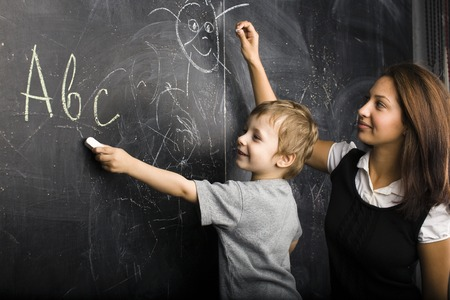 little cute boy in glasses with young real teacher, classroom studying at blackboard school kido close up Standard-Bild