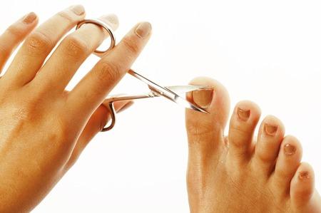 pedicura: manos de la mujer que hace la manicura no cualificado, pedicura a s� misma con herramientas aisladas Foto de archivo
