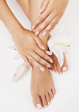 foot spa: manicure pedicure with flower lily close up isolated on white perfect shape hands spa salon