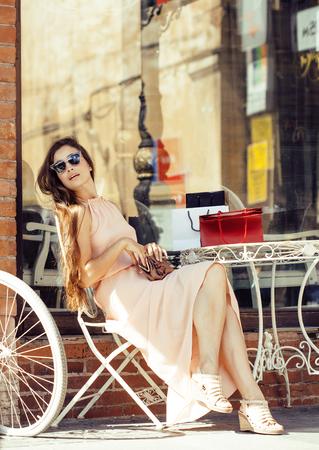 ropa de verano: bastante joven mujer morena después de las compras que se sienta en el café al aire libre en la calle sonriente, vestido con traje y gafas de sol, el horario de verano Foto de archivo