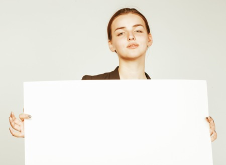 business costume: young pretty brunette girl with placard on white background wearing business costume student Stock Photo