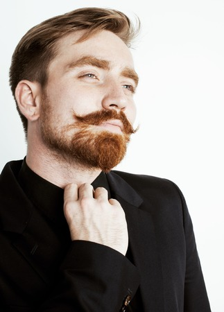 hair man: young red hair man with beard and mustache in black suit on white background close up