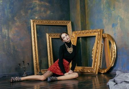 style: bellezza ricca donna bruna in interni di lusso nei pressi di cornici vuote, vintage eleganza close up di moda Archivio Fotografico
