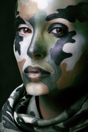 militaire sexy: Belle jeune femme de la mode avec des vêtements de style militaire et de la peinture de visage maquillage, les couleurs kaki, halloween célébration butin