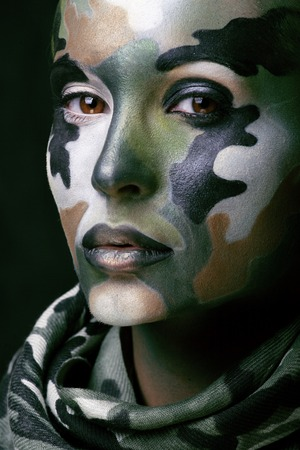 Beautiful young fashion woman with military style clothing and face paint make-up, khaki colors, halloween celebration swag