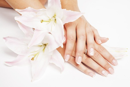manicure woman: beauty delicate hands with manicure holding flower lily close up isolated on white perfect shape Stock Photo