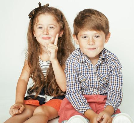gemelos ni�o y ni�a: peque�o muchacho lindo y ni�a abrazando juega en el fondo blanco, familia feliz cerca