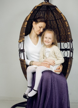 warm things: Portrait of mother and daughter at home, happy family in chair smiling