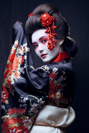 young pretty real geisha in kimono with sakura and decoration Stok Fotoğraf - 45665063