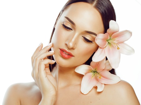 cuerpo perfecto femenino: joven y atractiva mujer de cerca con las manos en la cara aislada flor del lirio morena spa